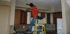 Water Damage Professional Working On A Ceiling Repair Job